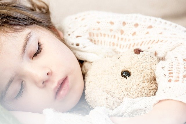 enfant qui dort avec sa peluche